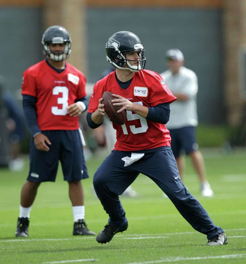 Seahawks quarterback Matt Flynn (15) passes as Russell Wilson (3) looks on. Photo: AP