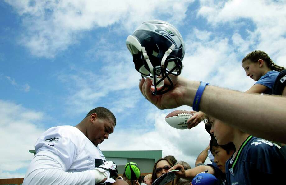 A fan holds up a miniature football helmet at right as Seahawks' defensive end Red Bryant signs auto