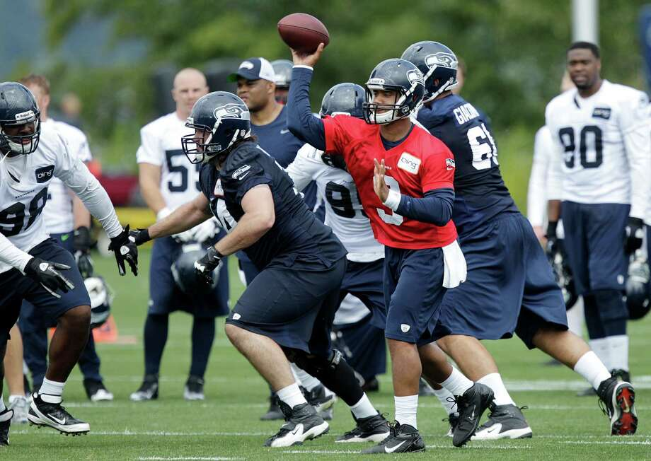 Seahawks quarterback Russell Wilson passes as John Moffitt, center left, blocks. Photo: AP