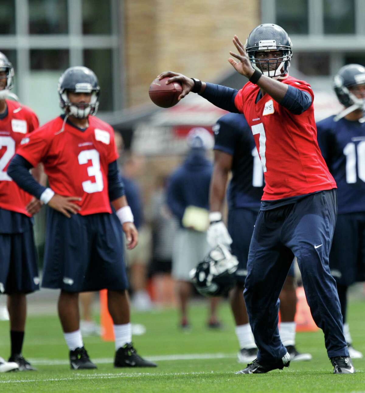 Seahawks quarterback Russell Wilson, (3) looks on as quarterback Tavaris Jackson, right, passes the ball.
