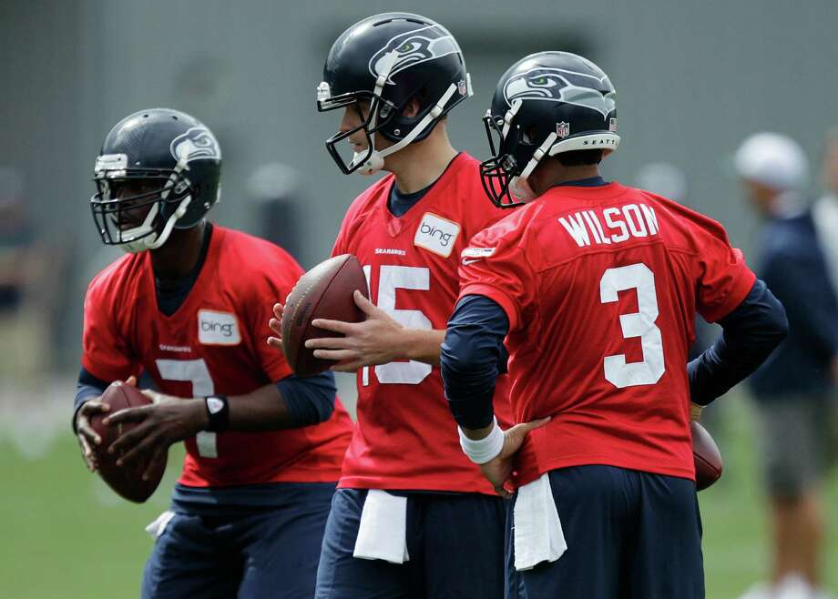 Seahawks quarterbacks Tavaris Jackson, left, Matt Flynn, center, and Russell Wilson, right, stand together on Saturday, the first day of NFL football training camp in Renton. Photo: AP