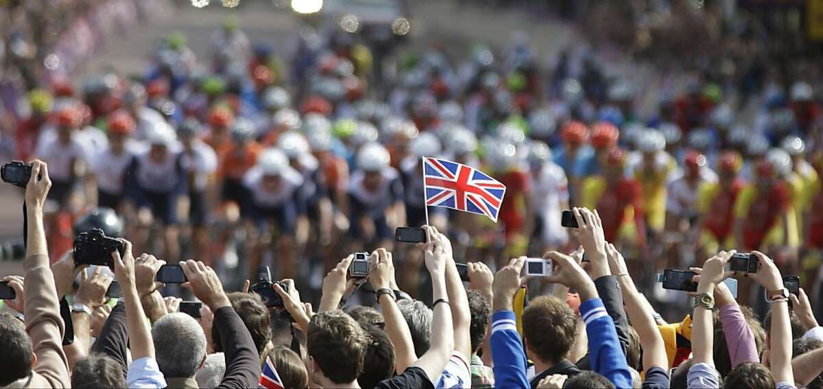 Spectators cheer and takes pictures as the pack ride past during the Men's Road Cycling race at the 2012 Summer Olympics, Saturday, July 28, 2012, in London. (AP Photo/Lefteris Pitarkis)
