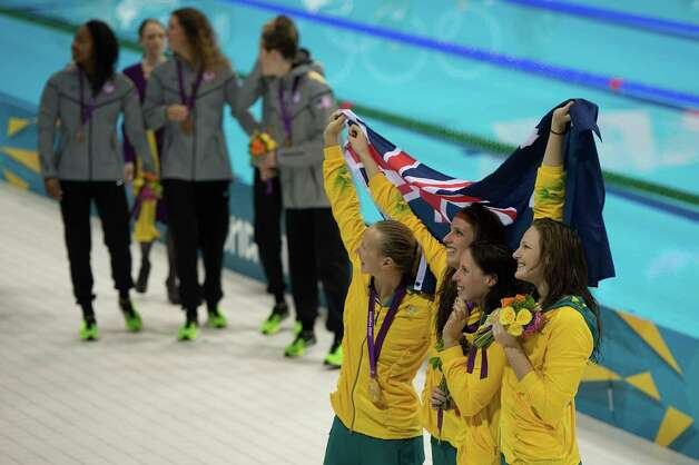 Members of Australia's 4x100-meter freestyle relay team wave to the crowd after winning the gold medal at the 2012 London Olympics on Saturday, July 28, 2012. The USA, at back, took bronze. Photo: Smiley N. Pool, Houston Chronicle / © 2012  Houston Chronicle