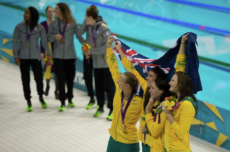 Members of Australia's 4x100-meter freestyle relay team wave to the crowd after winning the gold med