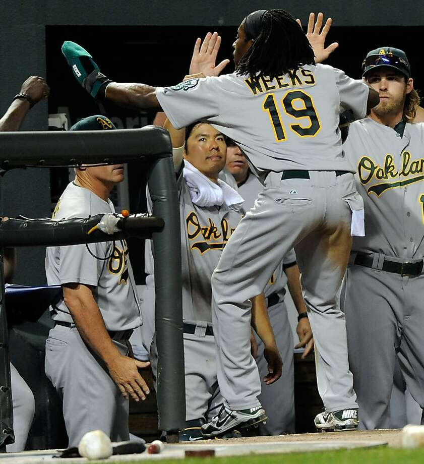 Oakland Athletics' Jemile Weeks (19) is greeted by teammates after scoring on a triple by Yoenis Cespedes in the eight inning of a baseball game against the Baltimore Orioles, Saturday, July 28, 2012, in Baltimore. The Athletics won 6-1. (AP Photo/Steve Ruark) Photo: Steve Ruark, Associated Press