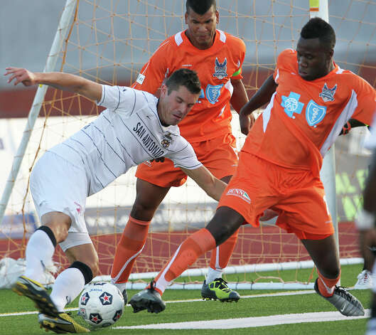 The Scorpions' Greg Janicki sneaks a shot past Carolina's Gale Aqbossoumonde (17) for the first goal as San Antonio plays the Railhawks at Heroes Stadium on Saturday, July 28, 2012. Photo: Tom Reel, San Antonio Express-News / ©2012 San Antono Express-News