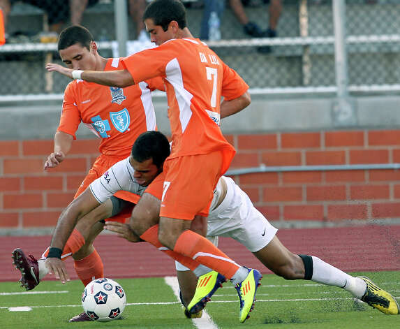 The Scorpions' Pablo Campos goes down battling between two Carolina defenders as San Antonio plays the Railhawks at Heroes Stadium on Saturday, July 28, 2012. Photo: Tom Reel, San Antonio Express-News / ©2012 San Antono Express-News