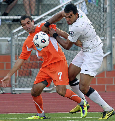 The Scorpions' Pablo Campos gets physical with Carolina's Austin Da Luz as San Antonio plays the Railhawks at Heroes Stadium on Saturday, July 28, 2012. Photo: Tom Reel, San Antonio Express-News / ©2012 San Antono Express-News