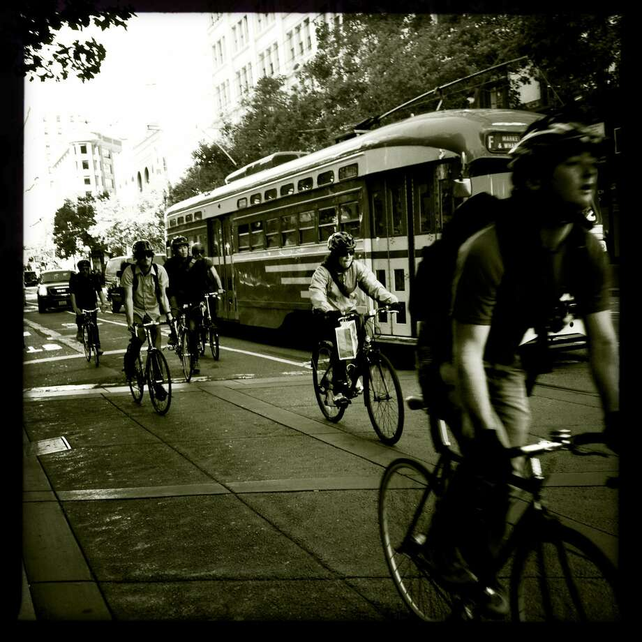 Morning bike commuters travel down Market Street in San Francisco, Calif. (The Chronicle)