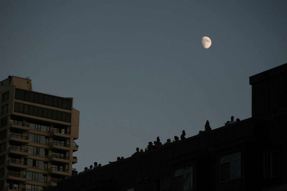The moon is seen over rooftop spectators during the Seafair Torchlight Parade on Saturday, July 28, 2012. Photo: JOSHUA TRUJILLO / SEATTLEPI.COM