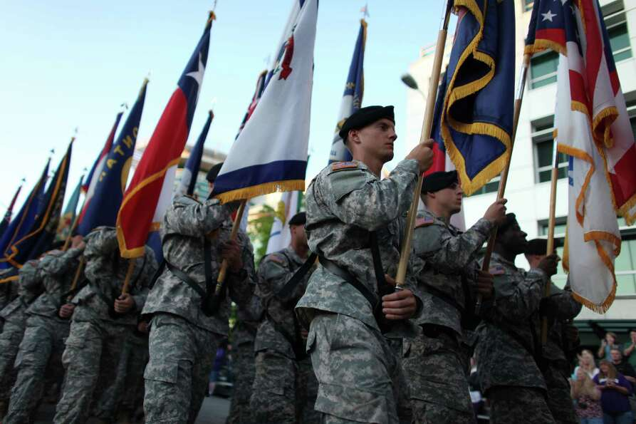 Members of the U.S. Army march with state flags during the Seafair Torchlight Parade on Saturday, Ju