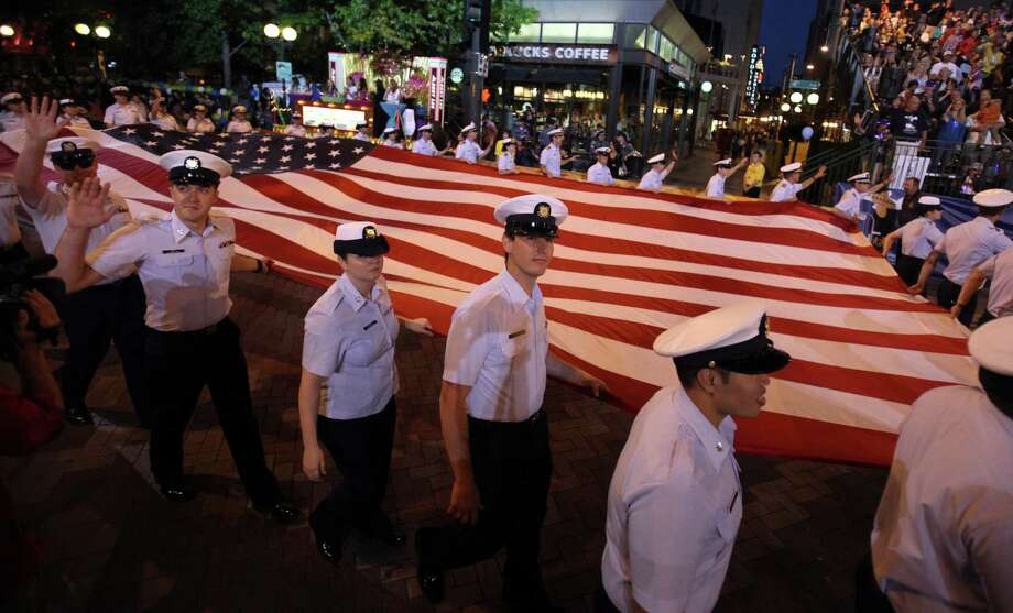 Members of the U.S. Coast Guard carry a flag during the Seafair Torchlight Parade on Saturday, July 28, 2012. Photo: JOSHUA TRUJILLO / SEATTLEPI.COM