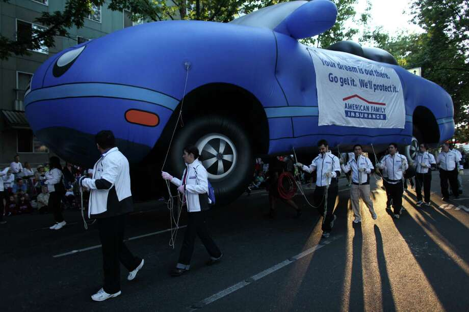 An inflatable car is maneuvered along the route during the Seafair Torchlight Parade on Saturday, July 28, 2012. Photo: JOSHUA TRUJILLO / SEATTLEPI.COM