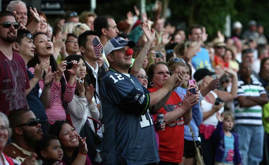 Spectators cheer and wave during the Seafair Torchlight Parade on Saturday, July 28, 2012. Photo: JOSHUA TRUJILLO / SEATTLEPI.COM