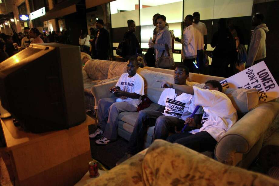 From left, Julian Anderson, 13, Jonn Brown, 18, and Jaylen Schmid, 14, play video games on a couch set up along the parade route during the Seafair Torchlight Parade on Saturday, July 28, 2012. Photo: JOSHUA TRUJILLO / SEATTLEPI.COM