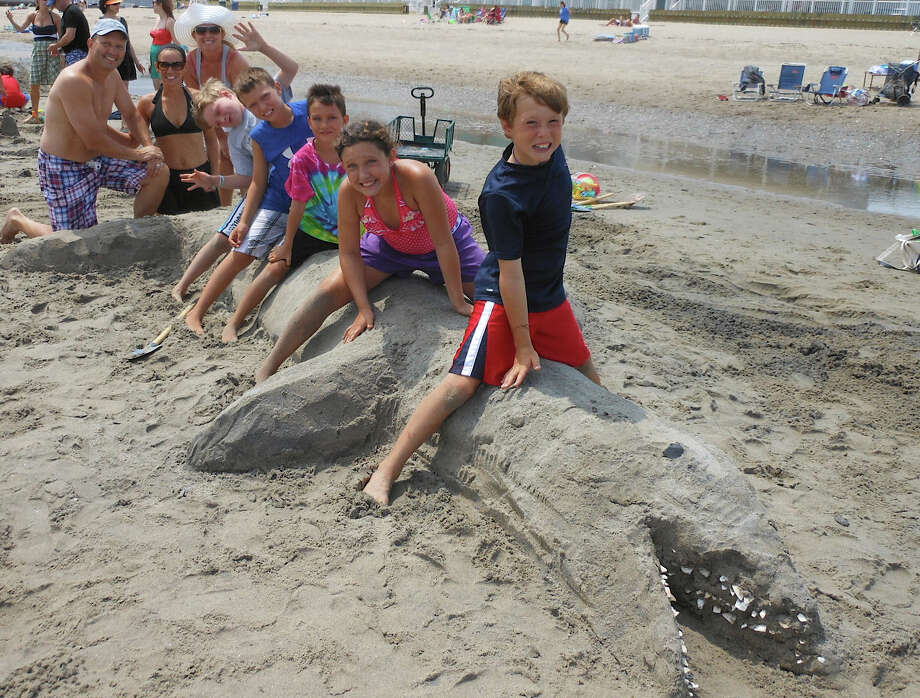 "The Gremse and Muller families of Fairfield straddle the  ""Shark Attack"" sand sculpture contest they made for the annual Fairfield Police Athletic League sandcastle contest on Saturday at Penfield Beach. Photo: Mike Lauterborn / Fairfield Citizen contributed"