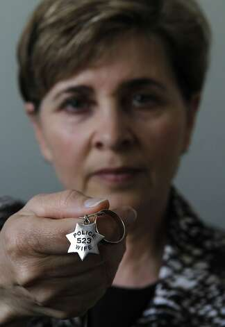 Nita Balousek holds a necklace with a pendant with her late husband's police badge number and his wedding ring at her home in Pleasant Hill, Calif. on Saturday, June 30, 2012. After her husband, Phil Balousek, an Oakland police officer with 27-years on the force, died from pancreatic cancer nearly two years ago, Nita is concerned about his pension plan that she counts on for her long-term financial security. Photo: Paul Chinn, The Chronicle