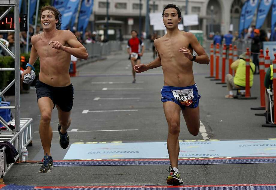 Robert Penney (left) and Gordon Rojas Kirby (right) had a race as they finished their marathon. The annual San Francisco Marathon starts and ends on the Embarcadero.  Marathon runners also ran across a foggy Golden Gate Bridge Sunday July 29, 2012. Photo: Brant Ward, The Chronicle