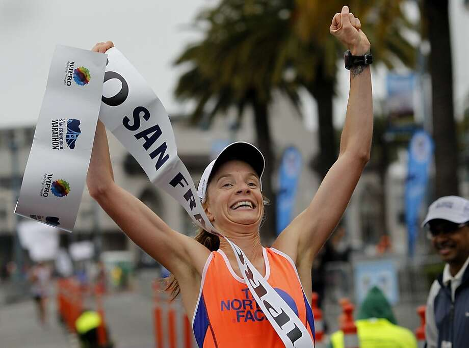 Devon Crosby-Helm celebrated her women's marathon victory at the finish line. The annual San Francisco Marathon starts and ends on the Embarcadero.  Marathon runners also ran across a foggy Golden Gate Bridge Sunday July 29, 2012. Photo: Brant Ward, The Chronicle