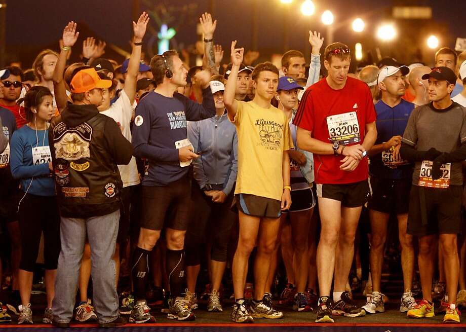 Runners raised their hands at the start if this was their first San Francisco Marathon. The annual San Francisco Marathon starts and ends on the Embarcadero.  Marathon runners also ran across a foggy Golden Gate Bridge Sunday July 29, 2012. Photo: Brant Ward, The Chronicle