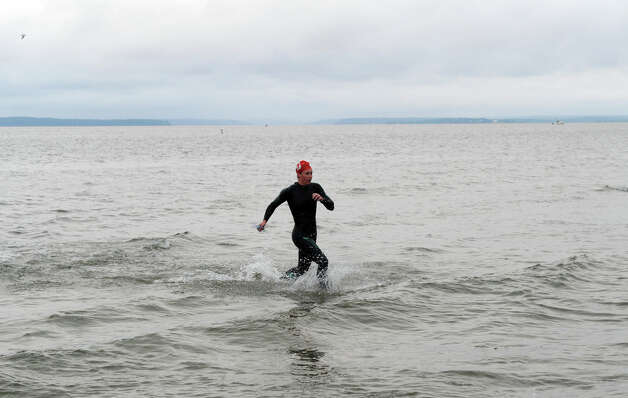 Megan Kelly races out of the water toward a win in the women's division in the Volvo of Stamford Greenwich Cup Triathlon at Tod's Point in Greenwich, Conn., July 29, 2012.  The triathlon begins with a half-mile swim at Greenwich Point, followed by a 15-mile bicycle ride and a 3-mile run. The triathlon, which is organized by Threads and Treads, is part of the Volvo of Stamford Greenwich Cup series of 10 races. Photo: Keelin Daly / Stamford Advocate