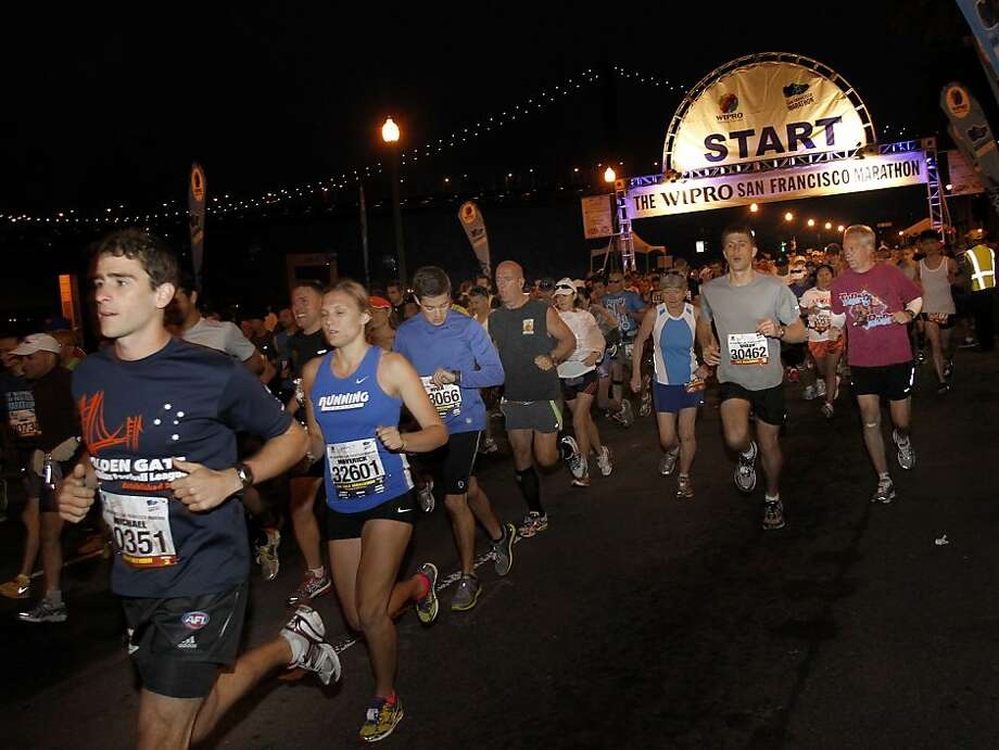 With the Bay Bridge in the background, marathon and half marathon runners take off early Sunday morning. The annual San Francisco Marathon starts and ends on the Embarcadero.  Marathon runners also ran across a foggy Golden Gate Bridge Sunday July 29, 2012. Photo: Brant Ward, The Chronicle