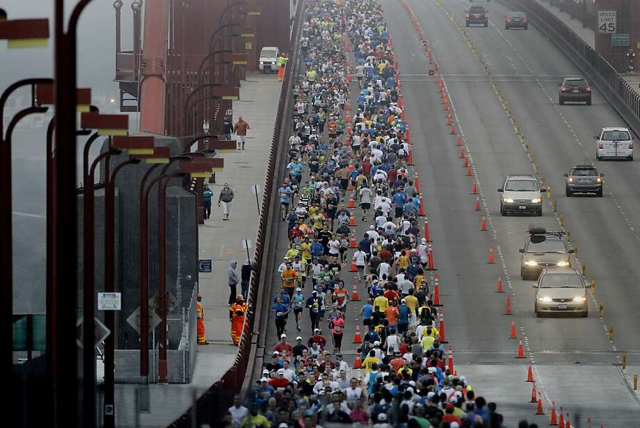 Marathon runners took up several lanes on the Golden Gate Bridge. The annual San Francisco Marathon starts and ends on the Embarcadero.  Marathon runners also ran across a foggy Golden Gate Bridge Sunday July 29, 2012. Photo: Brant Ward, The Chronicle