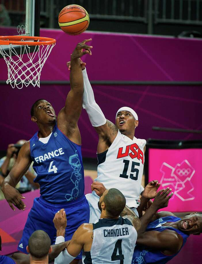 USA's Carmelo Anthony (15) scores over France's Kevin Seraphin during men's preliminary round basketball at the 2012 London Olympics on Sunday, July 29, 2012. Photo: Smiley N. Pool, Houston Chronicle / © 2012  Houston Chronicle