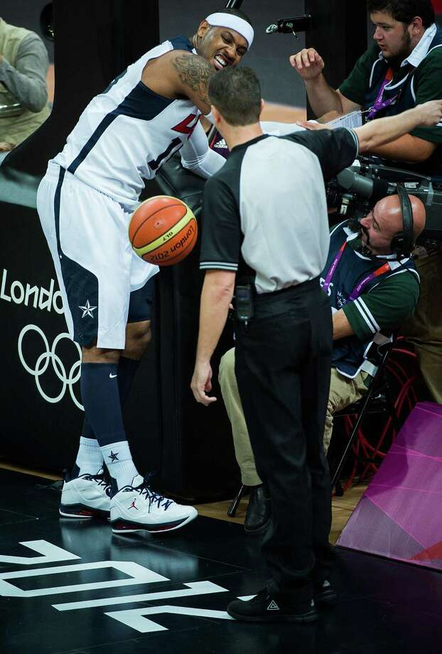 USA's Carmelo Anthony crashes into a television cameraman during men's preliminary round basketball against France at the 2012 London Olympics on Sunday, July 29, 2012. Photo: Smiley N. Pool, Houston Chronicle / © 2012  Houston Chronicle