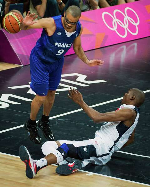 France's Tony Parker (9) loses the ball in a collision with USA's Kevin Durant during men's prelimin