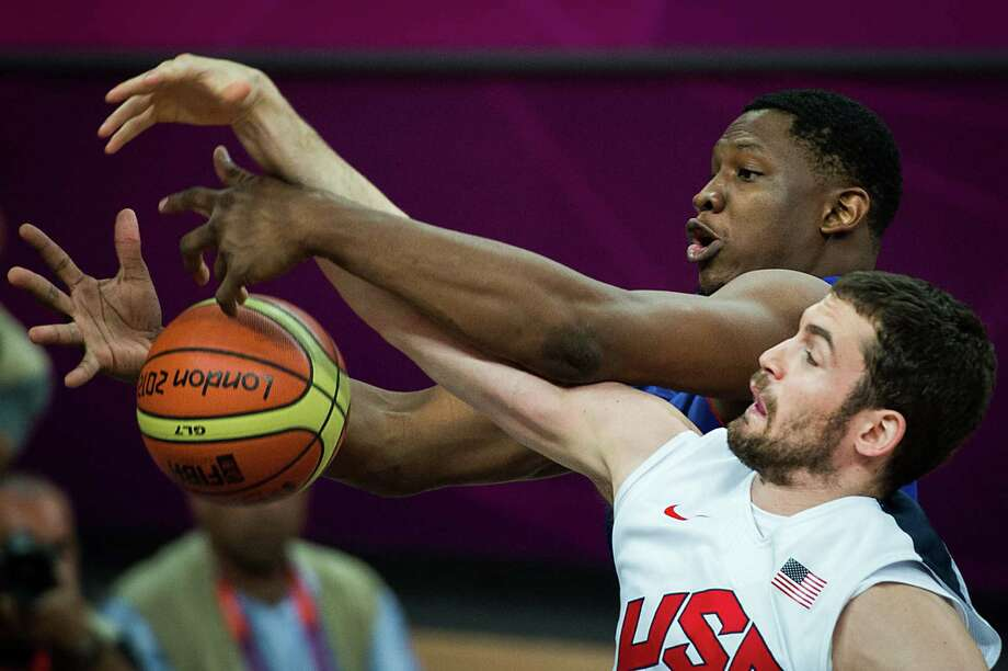 France's Kevin Seraphin, top, fights for a rebound against USA's Kevin Love during men's preliminary round basketball at the 2012 London Olympics on Sunday, July 29, 2012. Photo: Smiley N. Pool, Houston Chronicle / © 2012  Houston Chronicle