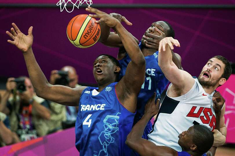 France's Kevin Seraphin (4) and Florent Pietrus (11) fight for a rebound against USA's Kevin Love du