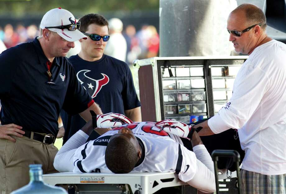 Dr. Walter Lowe, right, Houston Texans team doctor, checks on Houston Texans wide receiver Andre Johnson after Johnson suffered and injury during Texans training camp at the Methodist Training Center Sunday, July 29, 2012, in Houston. Johnson suffered a slight groin injury and was taken out of practice as a precaution, Texans head coach Gary Kubiak said. Photo: Brett Coomer, Houston Chronicle / © 2012 Houston Chronicle