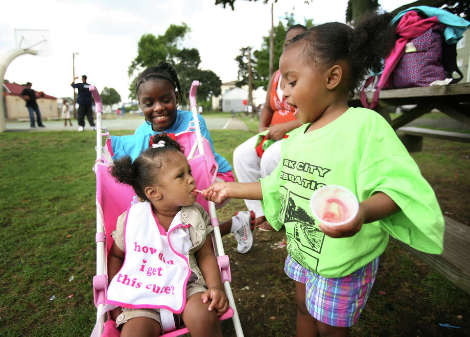 """From left; Nevaeh Enriquez, 1, Aaliyah Beason, 9, and Arianna Beason, 2, all of Bridgeport, enjoy some ice cream at the """"Park City Celebration"""" at Newfield Park in Bridgeport's East End on Sunday, July 29, 2012. Photo: Brian A. Pounds / Connecticut Post"""