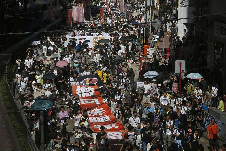 Thousands of people march on a downtown street in Hong Kong Sunday, July 29, 2012 to protest the upcoming introduction in schools of Chinese patriotism classes that they fear will lead to brainwashing. Teachers, parents, students and pro-democracy activists marched Sunday to the government headquarters of the semiautonomous territory to protest against the new curriculum, which authorities are encouraging schools to begin using when classes resume in September. (AP Photo/Vincent Yu) Photo: Vincent Yu, Associated Press