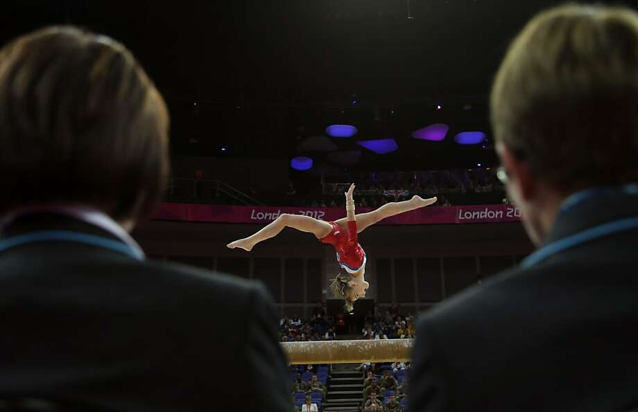 Judges watch Russian gymnast Anastasia Grishina perform on the beam during the Artistic Gymnastics women's qualification at the 2012 Summer Olympics, Sunday, July 29, 2012, in London. (AP Photo/Gregory Bull) Photo: Gregory Bull, Associated Press
