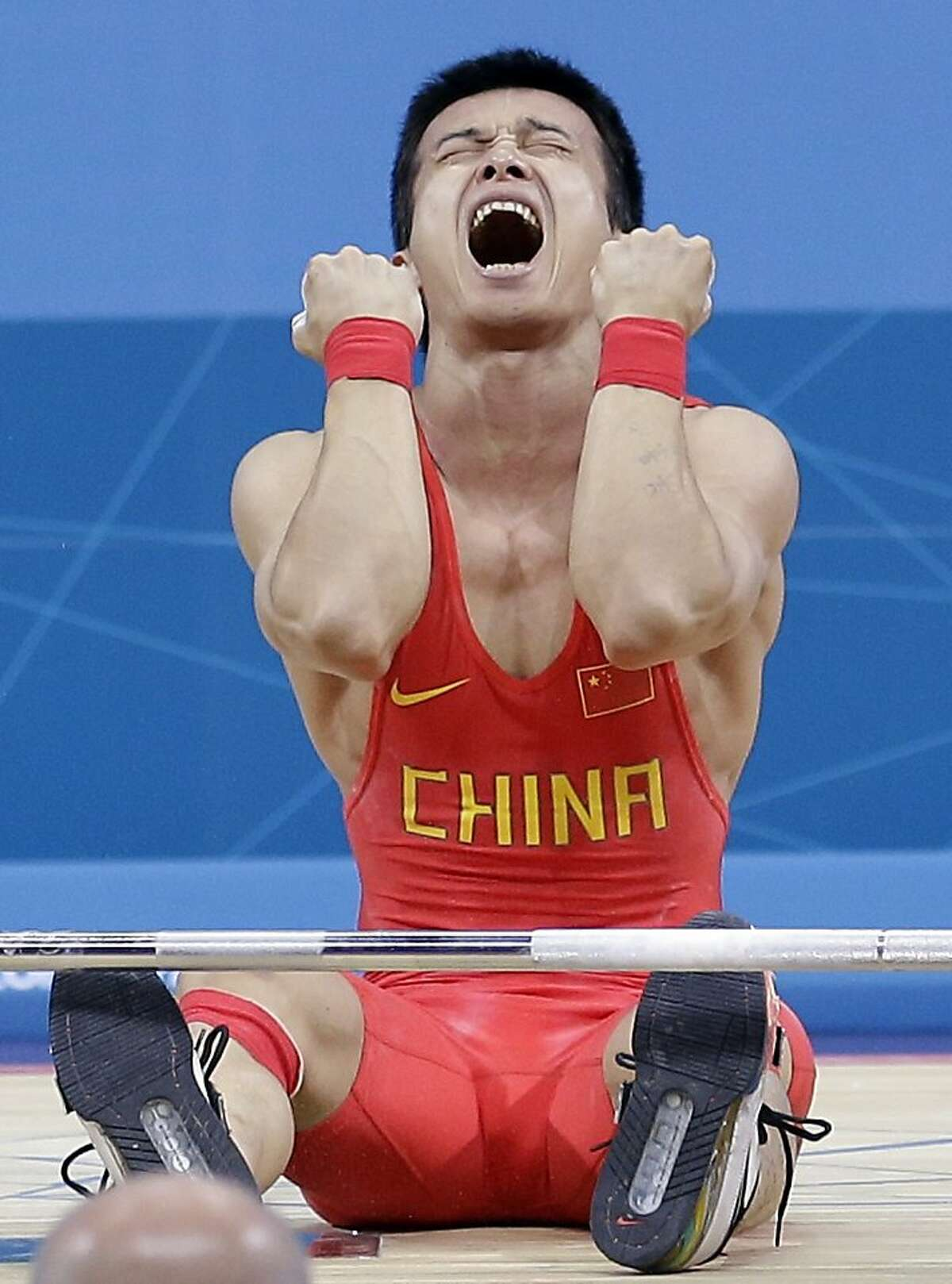 Jingbiao Wu of China reacts after failing to complete his final lift and falling into silver position during the mens 56-kg, group A, weightlifting competition at the 2012 Summer Olympics, Sunday, July 29, 2012, in London. (AP Photo/Hassan Ammar)