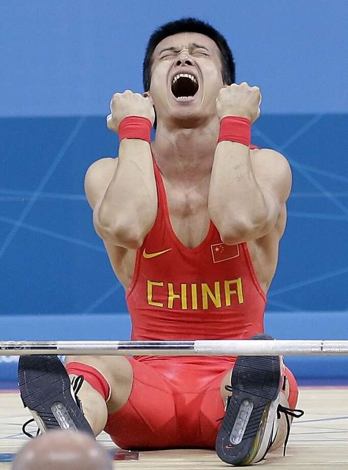 Jingbiao Wu of China reacts after failing to complete his final lift and falling into silver position during the mens 56-kg, group A, weightlifting competition at the 2012 Summer Olympics, Sunday, July 29, 2012, in London.  (AP Photo/Hassan Ammar) Photo: Hassan Ammar, Associated Press
