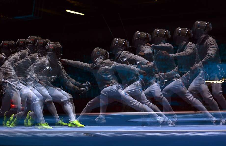 TOPSHOTS A multiple exposure picture taken on July 29, 2012 at the ExCel centre in London shows fencer fighting during a Men's Sabre fencing bout as part of the London 2012 Olympic games.     AFP PHOTO / ALBERTO PIZZOLIALBERTO PIZZOLI/AFP/GettyImages Photo: Alberto Pizzoli, AFP/Getty Images