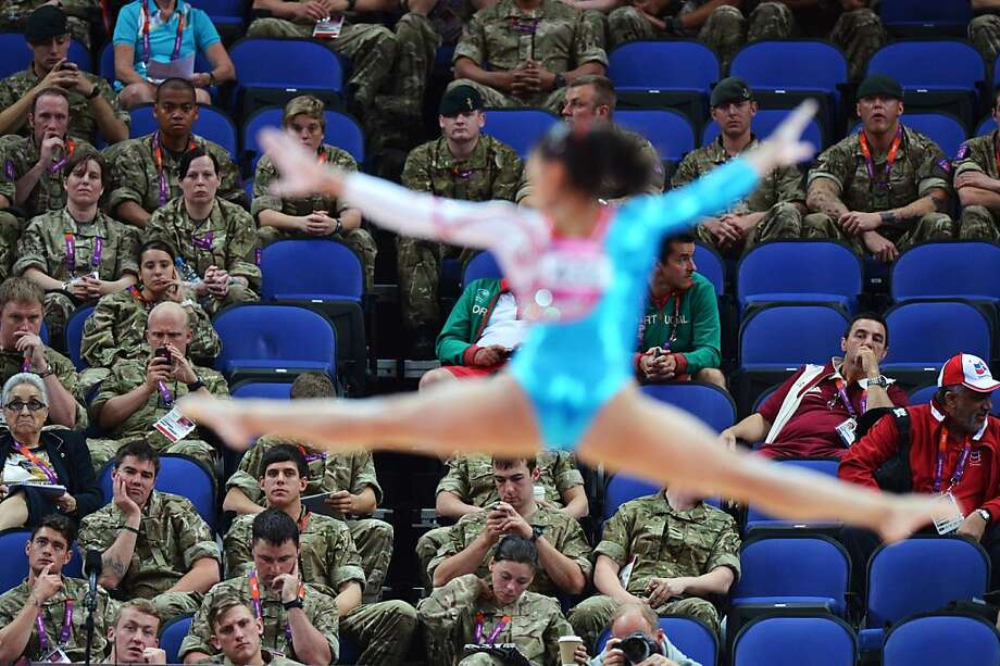 TOPSHOTS British soldiers watch a gymnast performing during the women's qualification of the artistic gymnastics event of the London Olympic Games on July 29, 2012 at the 02 North Greenwich Arena in London.  AFP PHOTO / BEN STANSALLBEN STANSALL/AFP/GettyImages Photo: Ben Stansall, AFP/Getty Images