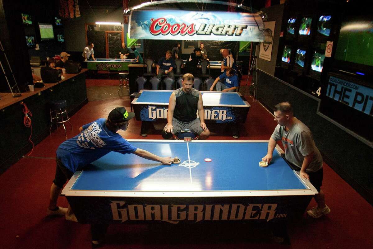 Chris Gibson, 15, (left) competes against David Parmley during the air hockey world championships at the SRO Family Sports Bar and Cafe on Saturday July 28, 2012 in Houston, Texas.