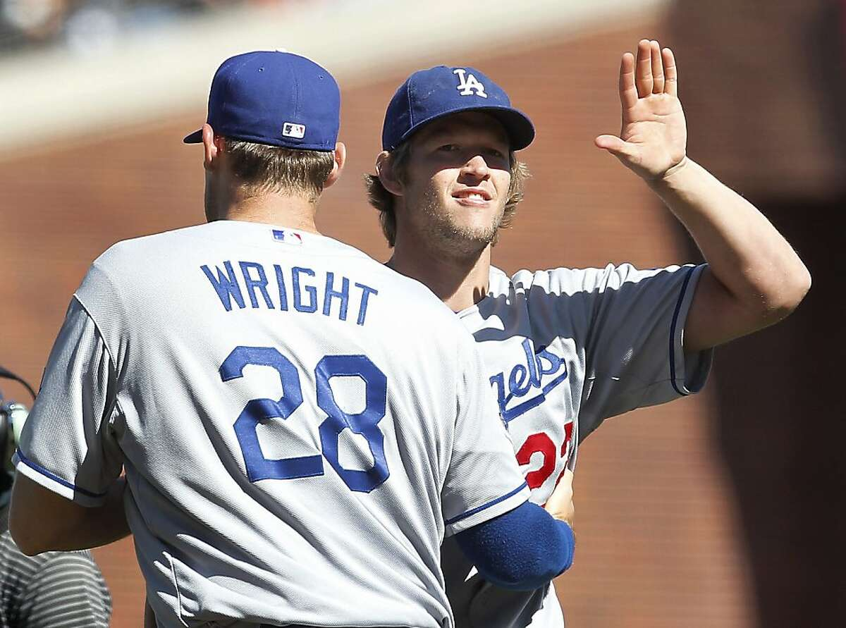 Los Angeles Dodgers starting pitcher Clayton Kershaw, right, is congratulated by teammate Jamey Wright (28) after a 4-0 victory against the San Francisco Giants in a baseball game in San Francisco, Sunday, July 29, 2012. (AP Photo/Tony Avelar)