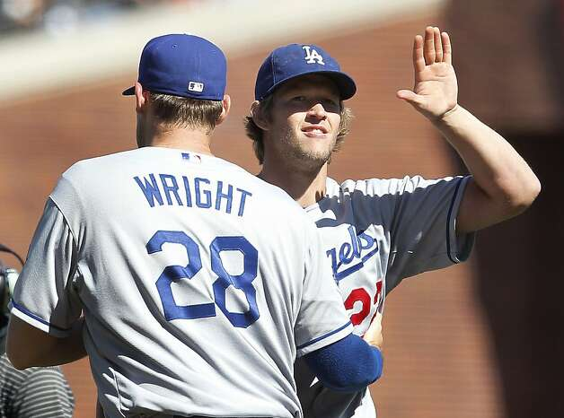 Los Angeles Dodgers starting pitcher Clayton Kershaw, right, is congratulated by teammate Jamey Wright (28) after a 4-0 victory against the San Francisco Giants in a baseball game in San Francisco, Sunday, July 29, 2012. (AP Photo/Tony Avelar) Photo: Tony Avelar, Associated Press