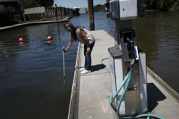 Korinne Flowers, who owns the Tracy Oasis Marina-Resort, uses a pole to show how low the water level is in Tracy, Calif., Friday, July 27, 2012.  Flowers is worried any plan to move water to existing pumps that supply water to Southern California, the Central Valley and the Bay Area will lower the water even more and hurt business. Photo: Sarah Rice, Special To The Chronicle