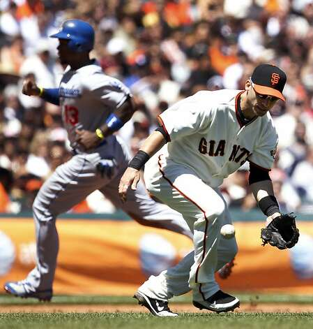 San Francisco Giants third baseman Marco Scutaro (19) drops a fly ball as Los Angeles Dodgers' Hanley Ramirez (13) advances to third base during the fourth inning of a baseball game in San Francisco, Sunday, July 29, 2012. (AP Photo/Tony Avelar) Photo: Tony Avelar, Associated Press
