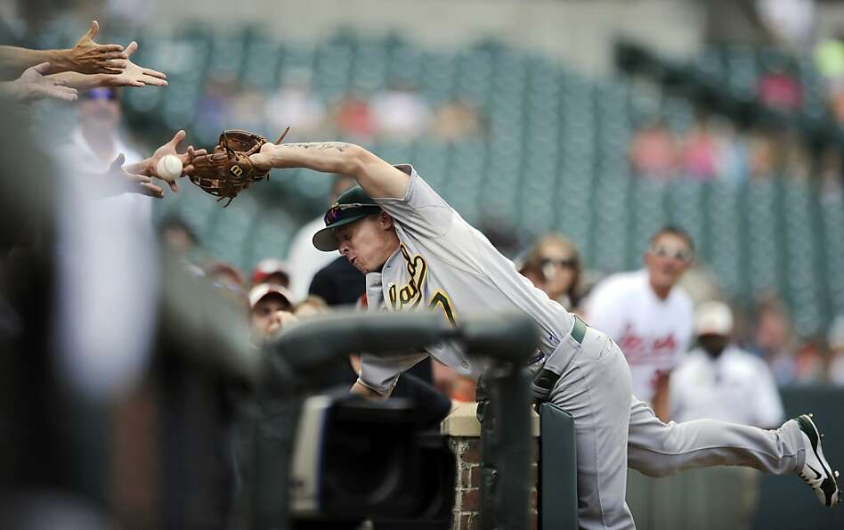Oakland Athletics third baseman Brandon Inge (7) dives into the stands in vain trying to get to a fo