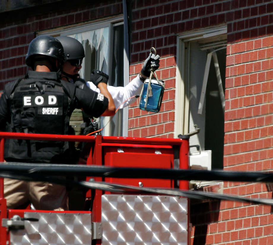 """Members of law enforcement prepare to place what ATF sources describe as a """"water shot"""" in the apartment of alleged Aurora, Colo., gunman James Holmes. The """"water shot"""" is placed near an IED and explodes. The blast is used to disable the IED. Photo: Alex Brandon / AP"""