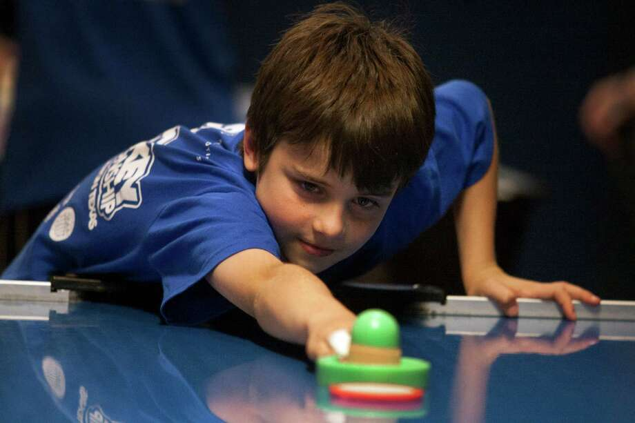 Felix Grabmayr, 9, stretches for the puck as he warms up during the air hockey world championships Saturday at the SRO Family Sports Bar and Cafe. Felix came with his dad and older brother from Seattle and competed in his very first youth division tournament. Photo: J. Patric Schneider / Houston Chronicle