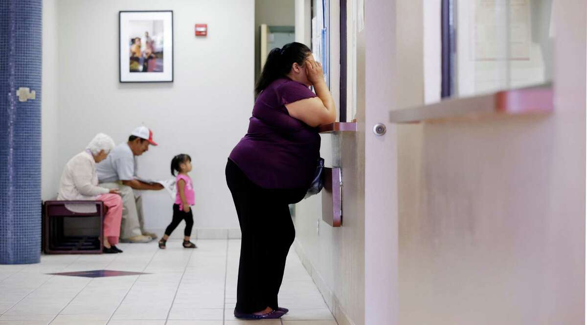 A woman stands at the registration window at Nuestra Clinica Del Valle in San Juan, where 85 percent of those served are uninsured. Texas offers coverage only to the disabled, children and low-income parents.