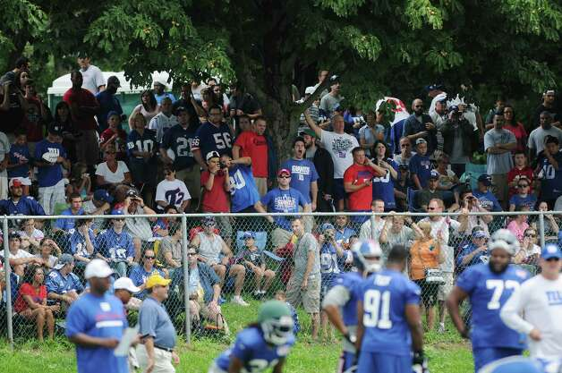 Fans watch from behind a fence during practice at New York Giants training camp at the University at Albany on Sunday, July 29, 2012 in Albany, NY.   (Paul Buckowski / Times Union) Photo: Paul Buckowski